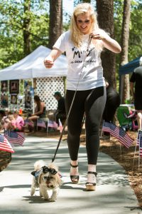 Snellville, GA, USA - May 14, 2016: A young woman proudly walks her dog in a dog fashion show at Pawfest, a dog festival on May 14, 2016 in Snellville, GA.